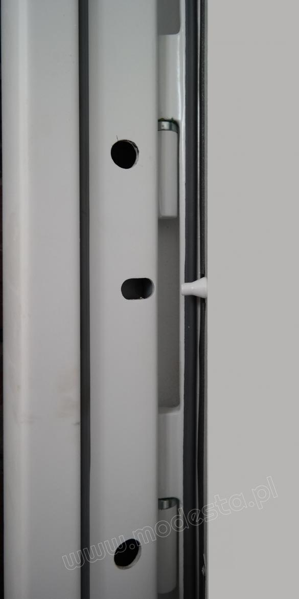 Entrance doors to a weaponry warehouse feature anti-burglar protection mounted at their hinges.
